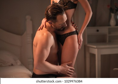 Sexy man sitting on bed and kissing her perfect body.