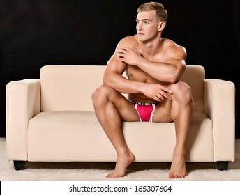 Sexy man sitting on sofa isolated on dark background