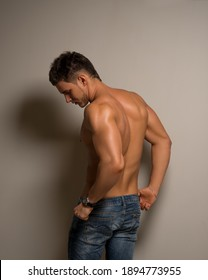 Sexy man standing back in studio. Muscled back of handsome young guy. Male model in jeans. Hunk in blue jeans.