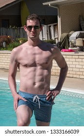 Sexy man standing by an outdoor swimming pool. Fit model with ripped abs in aviator sunglasses outside by swimming pool in the sun looking at the camera.