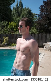 Sexy man standing by an outdoor swimming pool. Fit model with ripped abs in aviator sunglasses outside by swimming pool in the sun, 3/4 view, no shirt, in the summer.