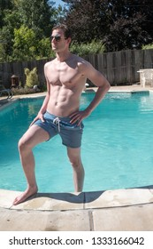 Sexy man standing on the steps of an outdoor swimming pool. Fit model with ripped abs in aviator sunglasses foot in the swimming pool, bright sunny day. Young hot guy in blue swimming suit.