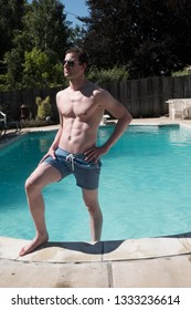 Sexy man standing on the steps of an outdoor swimming pool. Fit model with ripped abs in aviator sunglasses foot in the swimming pool, bright sunny day. Young hot guy in blue swimming suit by the pool