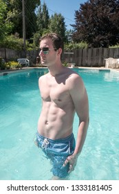 Sexy man standing in an outdoor swimming pool waist deep in water. Fit model with defined abs in aviator sunglasses foot in the swimming pool, bright sunny day. Young white man in blue swimming suit.