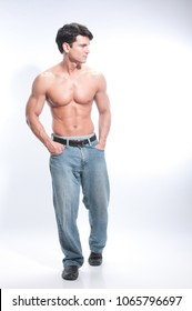 The sexy man is standing tall in his jeans.