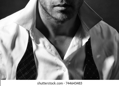 Sexy man with unshaven face in white shirt and red untied bow closeup