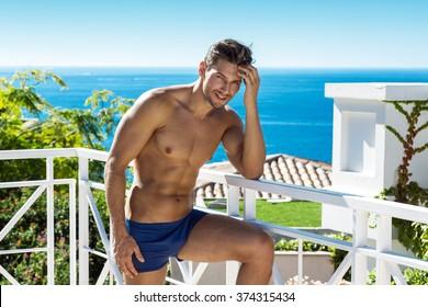 Sexy man wear swimming trunks posing in sea scenery
