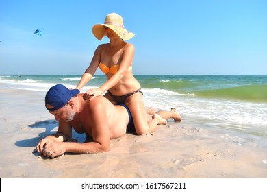 Sexy massage on the sea. The man ordered a massage on the beach. Couple fooling around on the beach. Romance. The couple on the island.