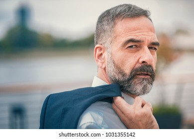 Sexy mature business man posing with his suit over his shoulder, outdoor portrait