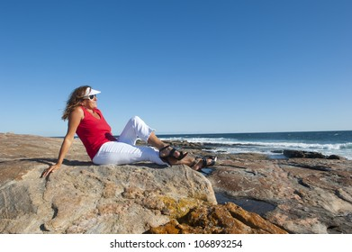 Sexy middle aged woman sitting at the ocean wearing red top, white pants and high heel shoes, isolated with happy relaxed smile and sea and blue sky as background and copy space.
