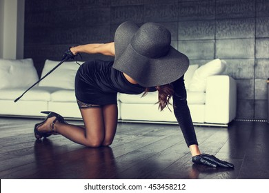 Sexy milf in hat kneeling on floor with whip, bdsm