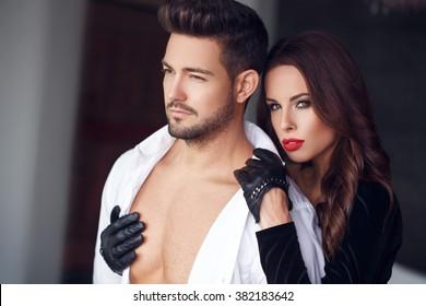 Sexy milf woman in gloves cuddle macho man indoor