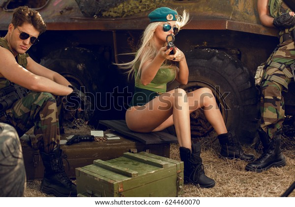 Sexy military blonde girl with sunglasses,green peaked cap and military look takes aim at the point.Horizontal view on the sexy soldiers background .