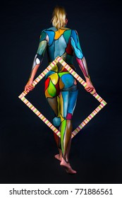 sexy model with back with bright body painting with frame on black background