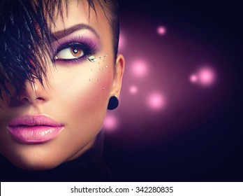 Sexy model girl face close up with holiday bright purple make up over black background. Beauty woman with vivid makeup and feather hairstyle. Beautiful Glamour lady. Party style