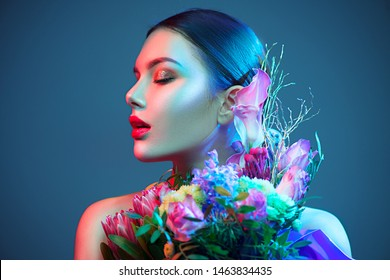 Sexy model girl with fashion bouquet of beautiful flowers in colourful fashion lights. Party. Beauty young woman with design bunch of flowers celebrating in Colorful neon lights, floral art design.