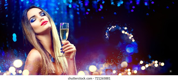 Sexy model girl with glass of champagne at party, drinking champagne over holiday glowing blue background. Beauty woman with perfect fashion makeup. Christmas and New Year holiday celebration.