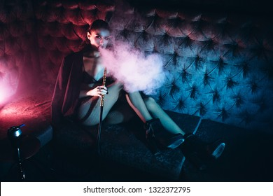 Sexy model in a night club smokes. Glamorous girl and perfect make up smoke a hookah. Beautiful Girl smoking a hookah. Neon light
