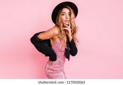 Sexy model with perfect shining wavy hairs in luxury sequin dress posing on pink background in studio.  Natural make up. Full sexy lips. Black hat and jacket. Fashionable portrait.
