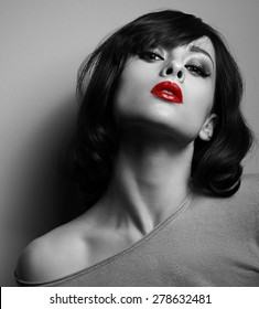 Sexy model with short hair style and red lips posing on dark background. Black and white