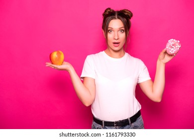 Sexy model with stylish hairstyle in white t-shirt on a pink background. Emotional portrait. She shocked, amazed, tying to choose between good and bad food: apple or donut?