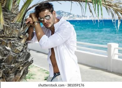 Sexy model wearing white shirt in aviator sunglasses