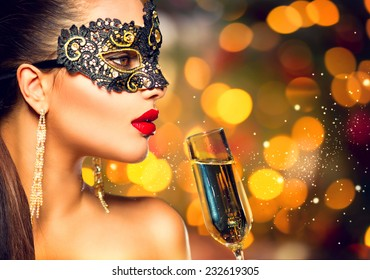 sexy model woman with glass of champagne wearing venetian masquerade carnival mask at party drinking