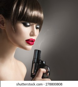 Sexy model woman with a gun. Beauty girl portrait, beautiful lady with revolver. Perfect makeup and fringe hairstyle, red lips