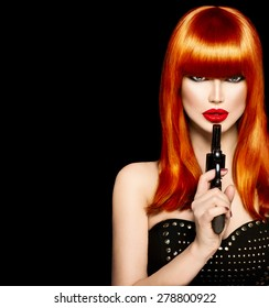 Sexy model woman with a gun. Beauty girl portrait, beautiful lady with revolver. Perfect long red hair, fringe hairstyle, red lips. Makeup. Isolated on Black background
