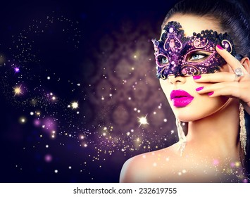 Sexy model woman wearing venetian masquerade carnival mask at party over holiday dark background. Christmas and New Year celebration. Sexy girl with holiday makeup and manicure. Purple lips and nails
