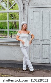 Sexy modern bride in white cylinder hat lstanding next to old white vintage door and mirror window. Copy space.