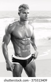 Sexy muscle fit male model in swimsuit on beach