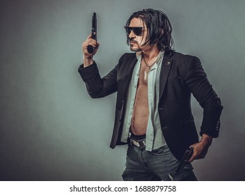sexy muscular body model portrait of a young man holding a gun in his hands