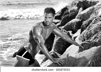 Sexy muscular bodybuilder posing near rocks and ocean