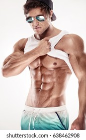 Sexy muscular fitness man showing sixpack muscles without fat over white background