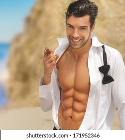 Sexy muscular handsome man with big smile and open shirt holding cigar