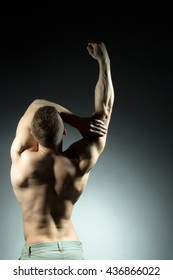 Sexy muscular male back of athlete bodybuilder posing in power with raised hands and bare torso on grey background