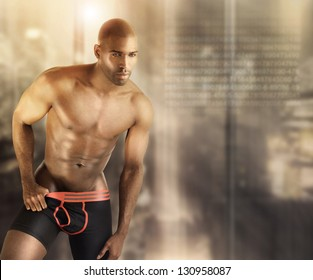 Sexy muscular male model in underwear against modern futuristic abstract background with lots of copy space