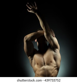 Sexy muscular male torso of athlete bodybuilder posing in power with veins on hands and bare chest on grey background