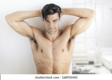 Sexy muscular man in bright modern interior