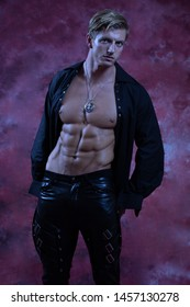 Sexy, muscular man in goth-like clothes, against a red and crimson background.