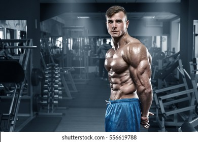 Sexy muscular man in gym, shaped abdominal, showing muscles. Bodybuilder male naked torso abs, working out