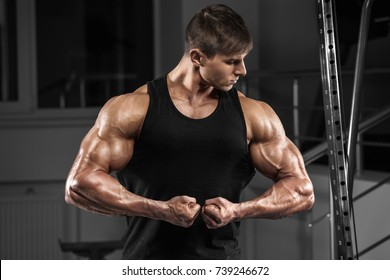 Sexy muscular man in gym, working out. Strong male showing biceps
