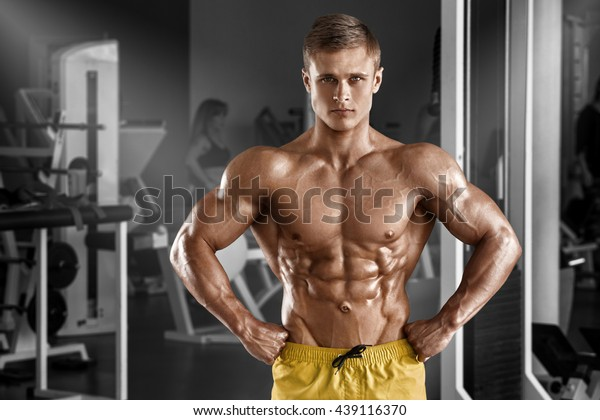 Brutal Strong Bodybuilder Man Posing In Studio On Grey