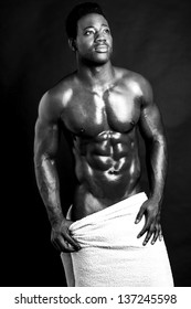 Sexy muscular man wrapped in a white towel. Black and white image.