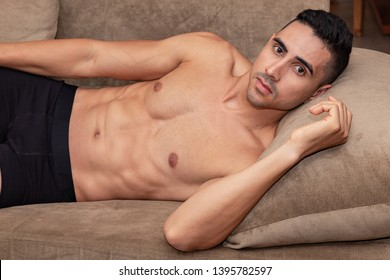 Sexy and muscular young man lying on the couch wearing only a black underwear.