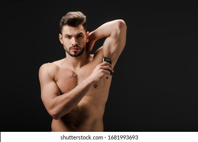 sexy naked man applying deodorant on armpit isolated on black