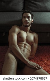 sexy and naked muscular young man posing on the floor near the sofa