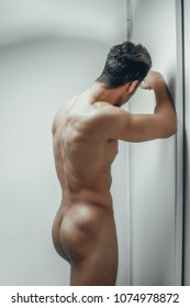sexy and naked muscular young man posing standing in the room