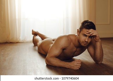sexy and naked muscular young man posing on the floor